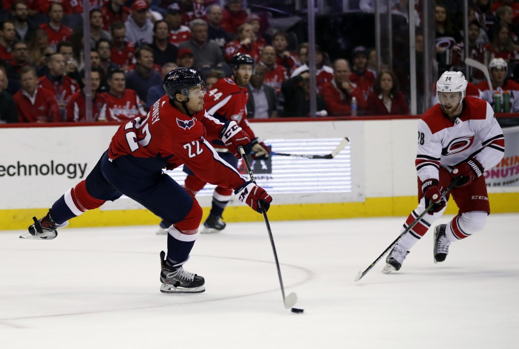 Washington Capitals defensemen Madison Bowey (22) passes the puck past Carolina Hurricanes center Elias Lindholm (28), from Sweden, in the second peri