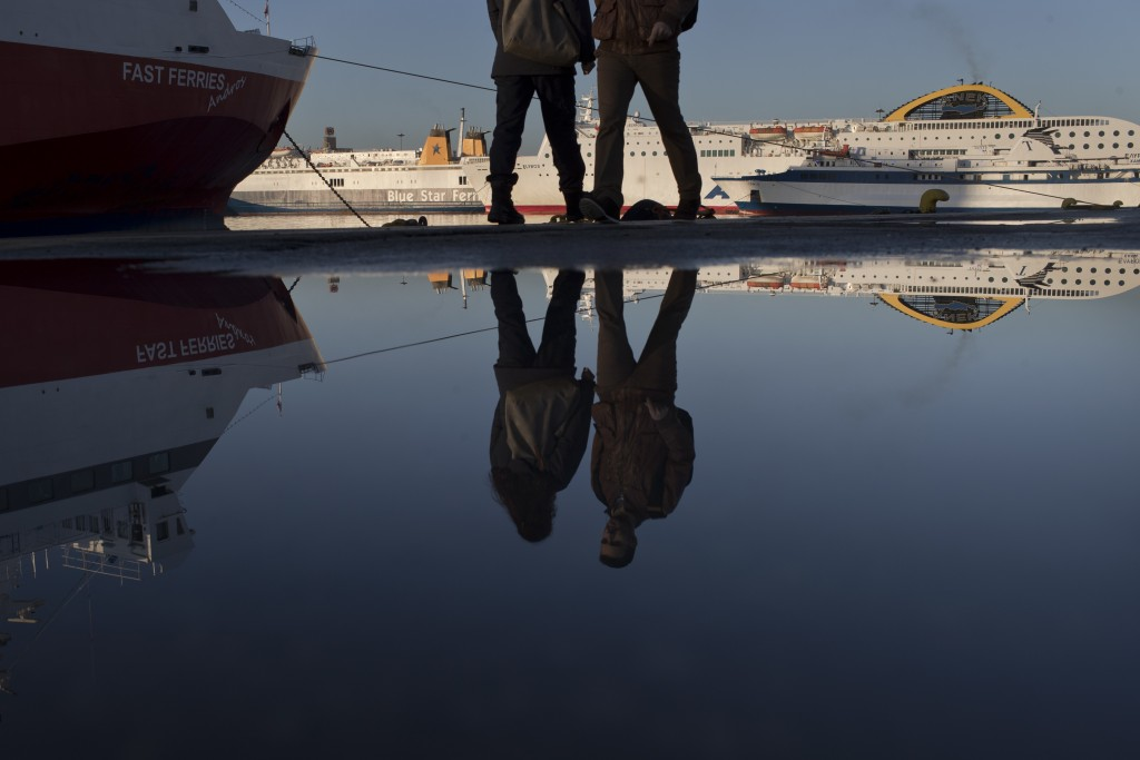 Pedestrians are reflected in water in front of docked ferries at the port of Piraeus near Athens during a 24-hour strike, Friday, Jan. 12, 2018. Greek