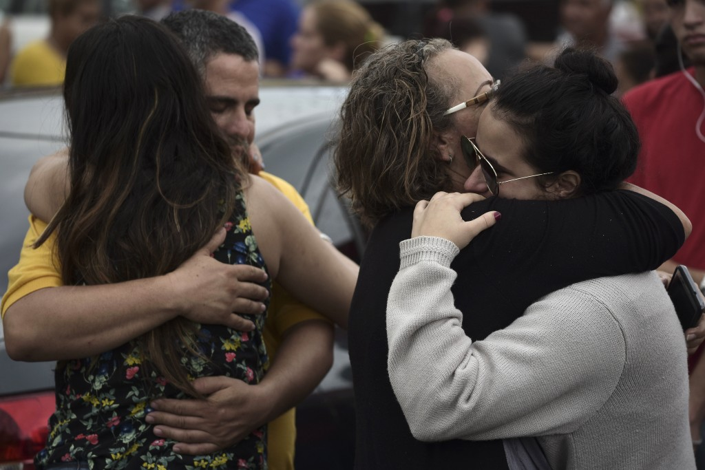 Relatives comfort each other as the body of a family member is removed at an early morning crime scene, in San Juan, Puerto Rico, Thursday, Jan. 11, 2