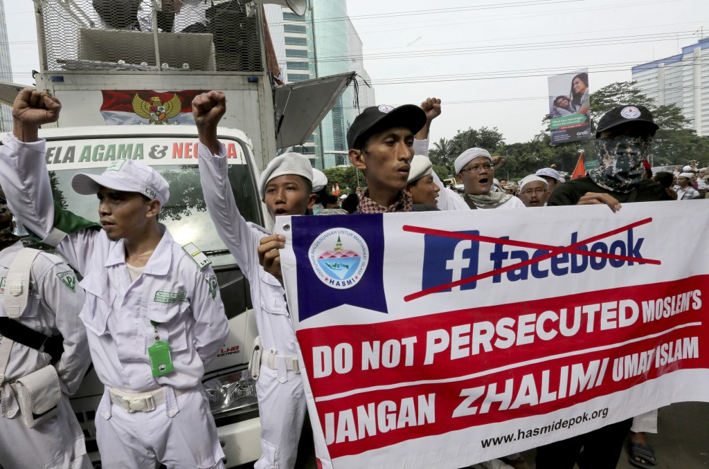 A group of Muslims hold a banner during a rally outside the Facebook office in Jakarta, Indonesia, Friday, Jan. 12, 2018. Muslim hard-liners have stag