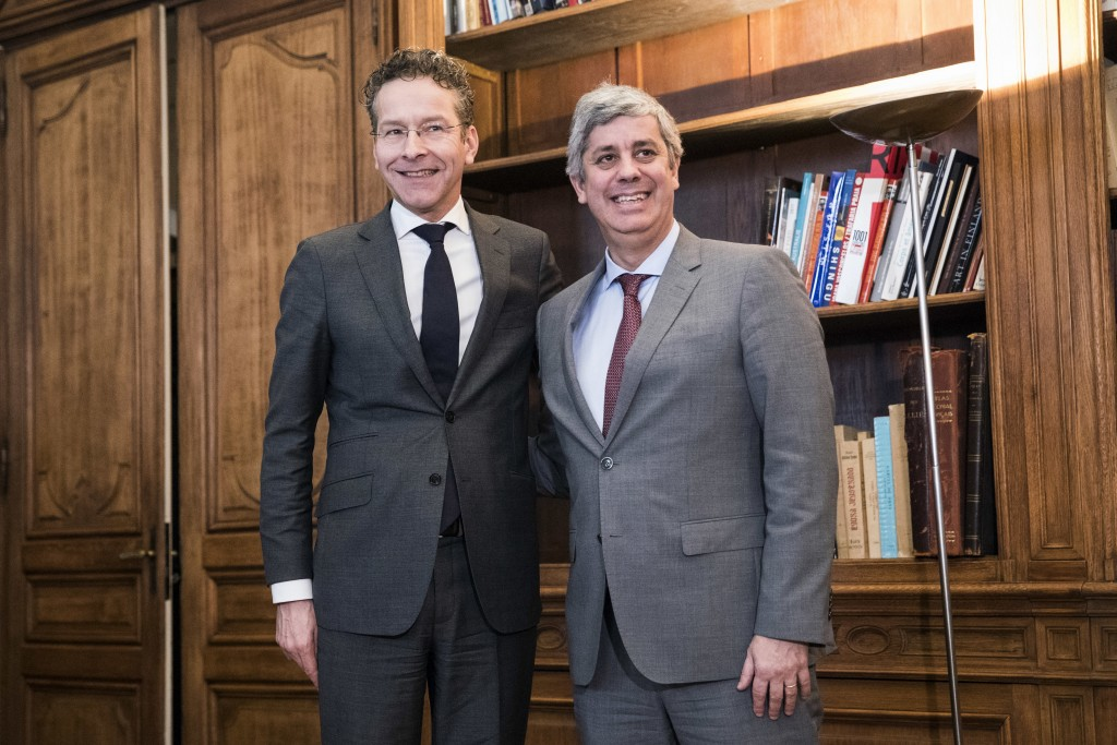 Outgoing leader Jeroen Dijsselbloem, left, of the Netherlands smiles after handing over power of the so-called eurogroup to Portugal's Mario Centeno,