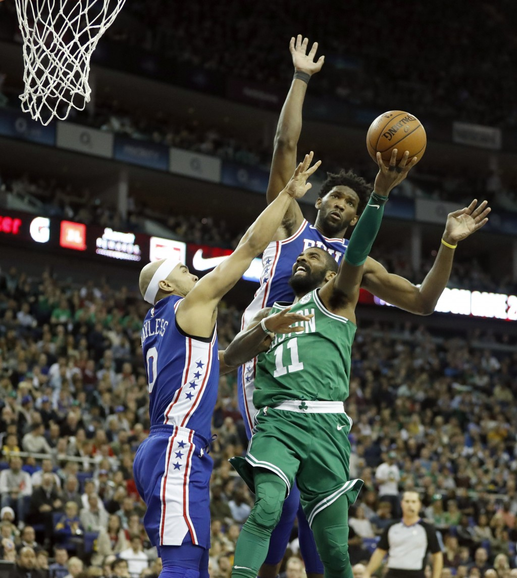 Boston Celtics guard Kyrie Irving, center, goes up for a layup while being blocked by Philadelphia 76ers guard Jerryd Bayless, left, during an NBA bas