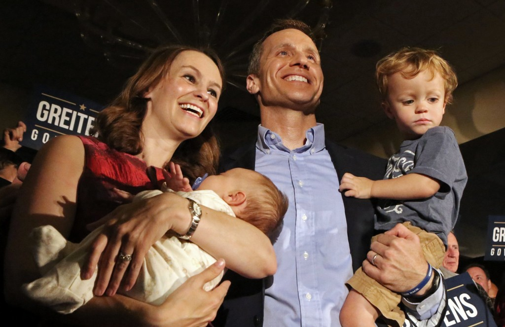 In this Aug. 2, 2016, photo, Eric Greitens poses with his wife, Sheena and his two sons Jacob and Joshua at a watch party at the Doubletree Hotel in C