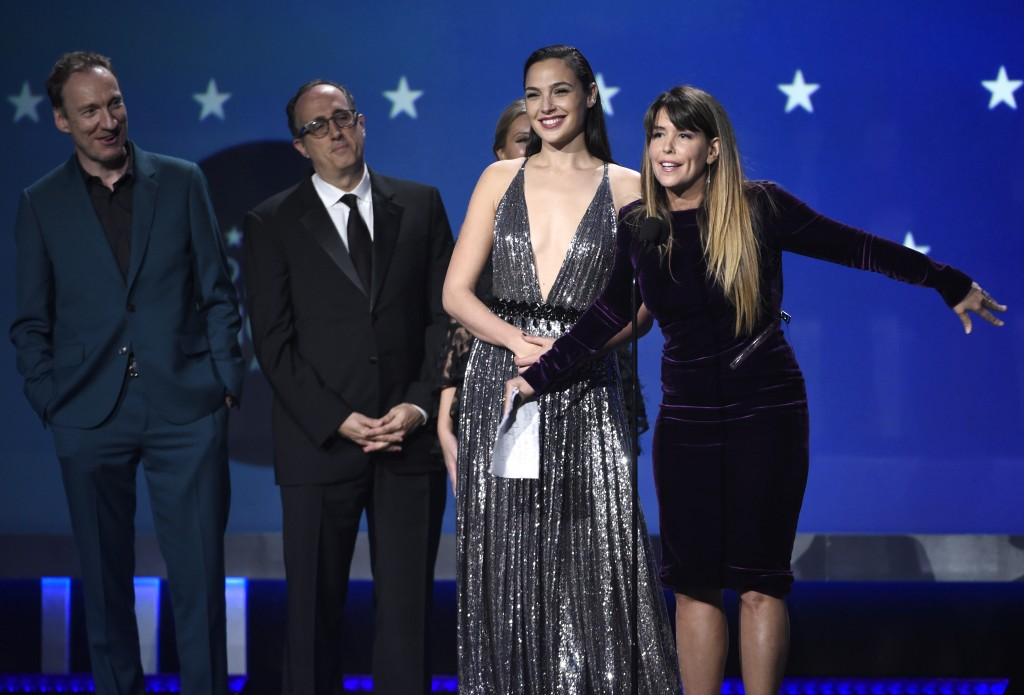 """Gal Gadot, center, Patty Jenkins and the crew of """"Wonder Woman"""" accept the award for best action movie at the 23rd annual Critics' Choice Awards at th"""