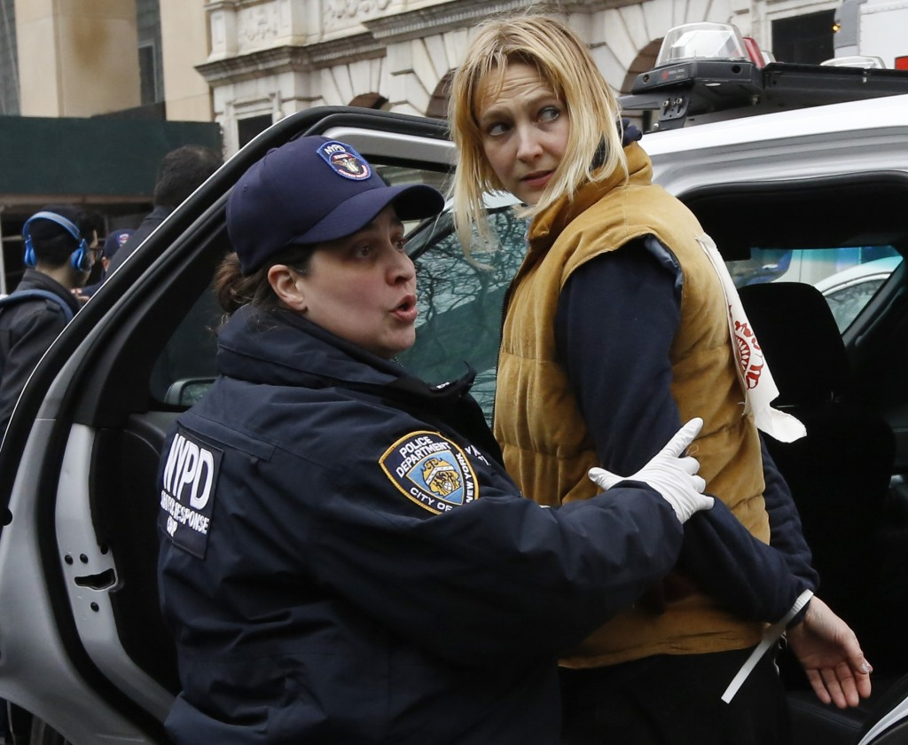 A New York City Police officer shouts to a colleague as she leads protester Maria Hunken to a squad car after Hunken and others were arrested demonstr