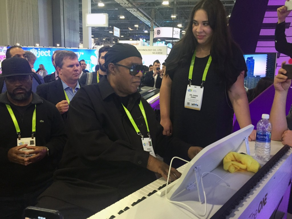 """In this Wednesday, Jan. 10, 2018, photo, musician Stevie Wonder plays a so-called """"smart"""" piano, an internet-connected device designed to teach people"""