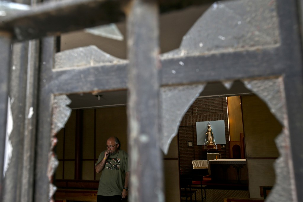 A church employee surveys the damage caused by an overnight fire bomb attack at the Emmanuel Catholic Church, in Santiago, Chile, Friday, Jan. 12, 201