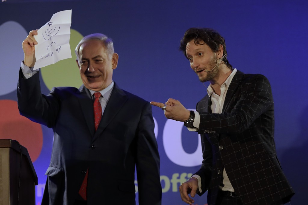 In this photo dated Wednesday, Jan. 10, 2018, Israeli mentalist Lior Suchard, right, gestures as he stands with Israeli Prime Minister Benjamin Netany