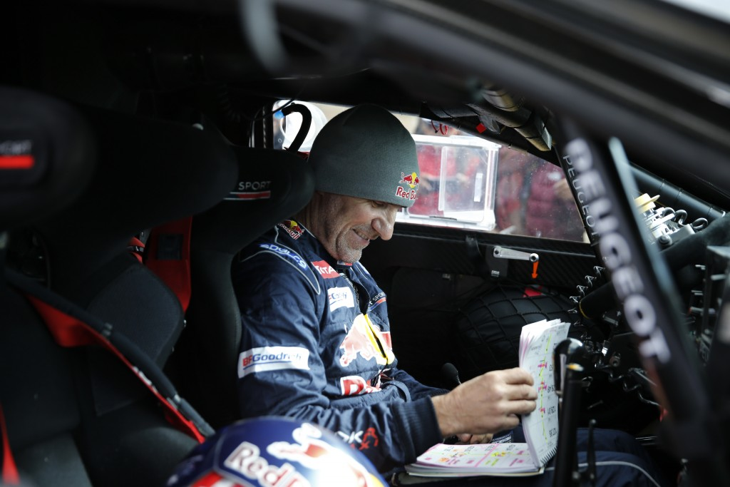 Driver Stephane Peterhansel, of France, sits in his Peugeot checking the road book during the 6th stage of the 2018 Dakar Rally between Arequipa, Peru