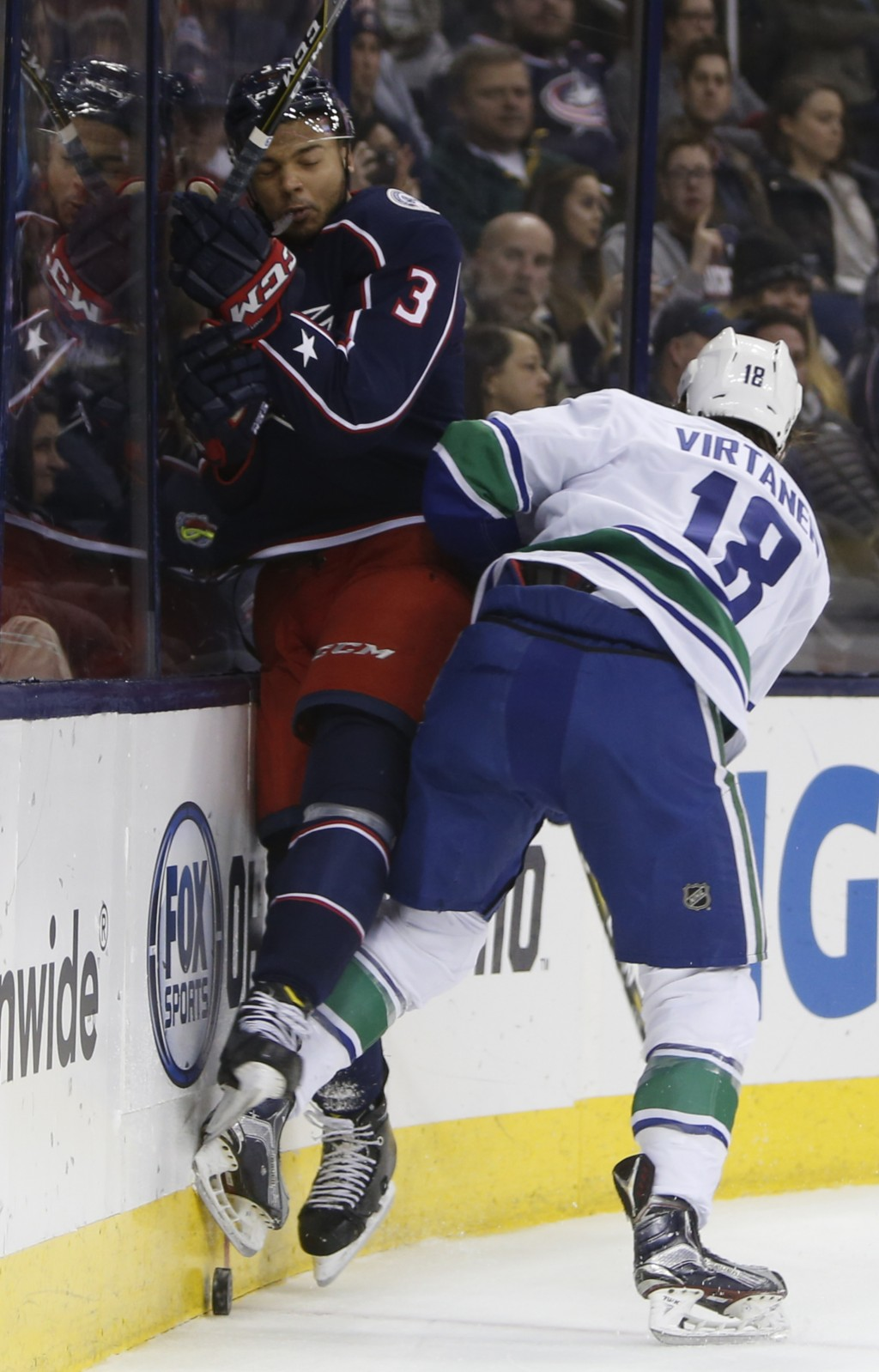 Vancouver Canucks' Jake Virtanen, right, checks Columbus Blue Jackets' Seth Jones during the first period of an NHL hockey game Friday, Jan. 12, 2018,