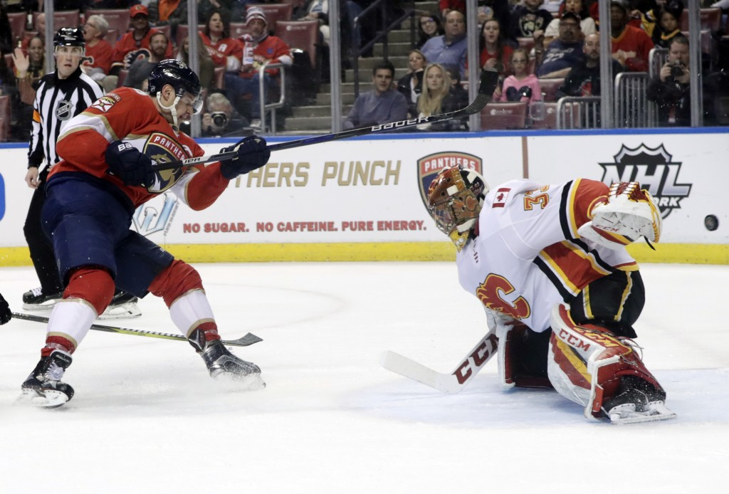 Florida Panthers' Aleksander Barkov, left, makes an attempt at the goal as Calgary Flames goaltender David Rittich (33) defends during the second peri