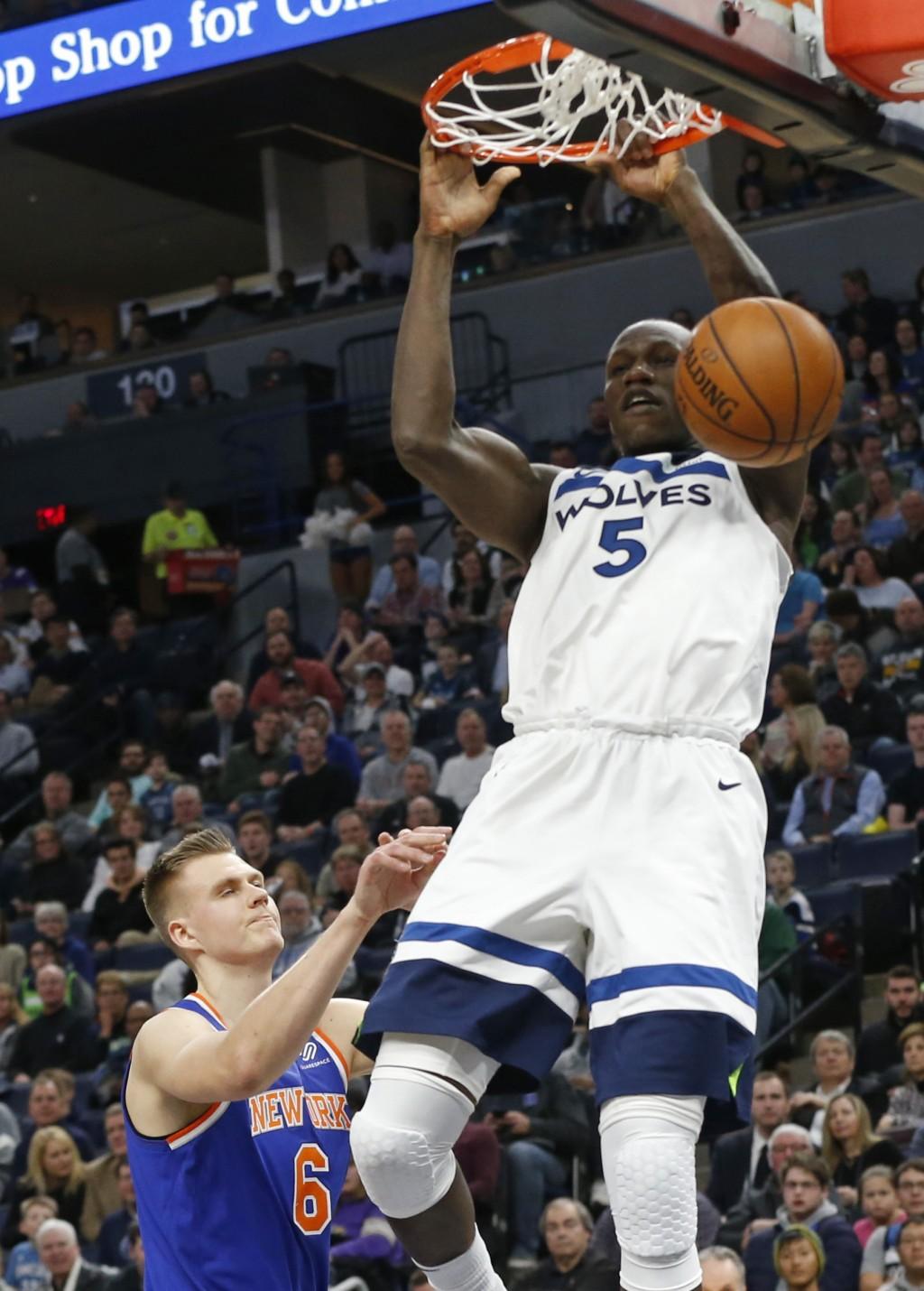Minnesota Timberwolves' Gorgui Dieng, right, of Senegal, dunks as New York Knicks' Kristaps Porzingis, of Latvia, looks on in the first half of an NBA