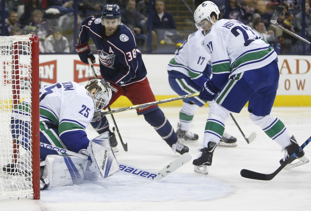 Vancouver Canucks' Jacob Markstrom, left, of Sweden, makes a save as teammate Ben Hutton, right, and Columbus Blue Jackets' Boone Jenner look for the