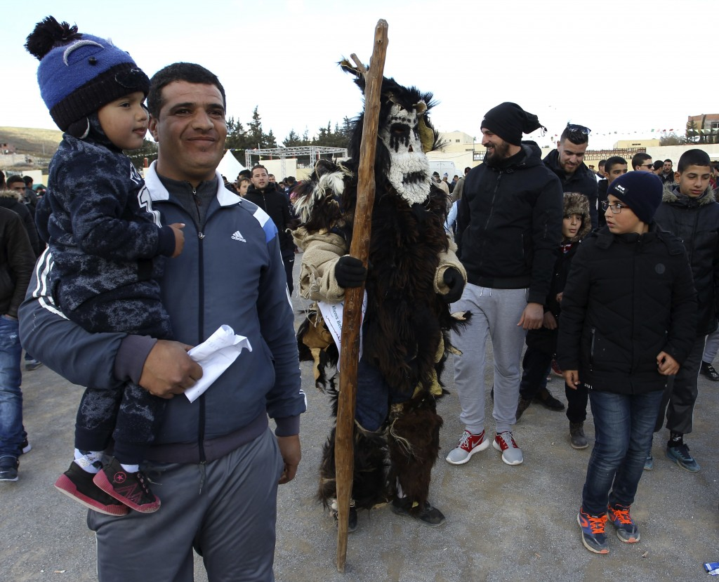 Performers dressed in animal-hide costumes meet residents during the Ayred festival in the village of Beni Snous, south of Tlemcen, Algeria, Thursday,