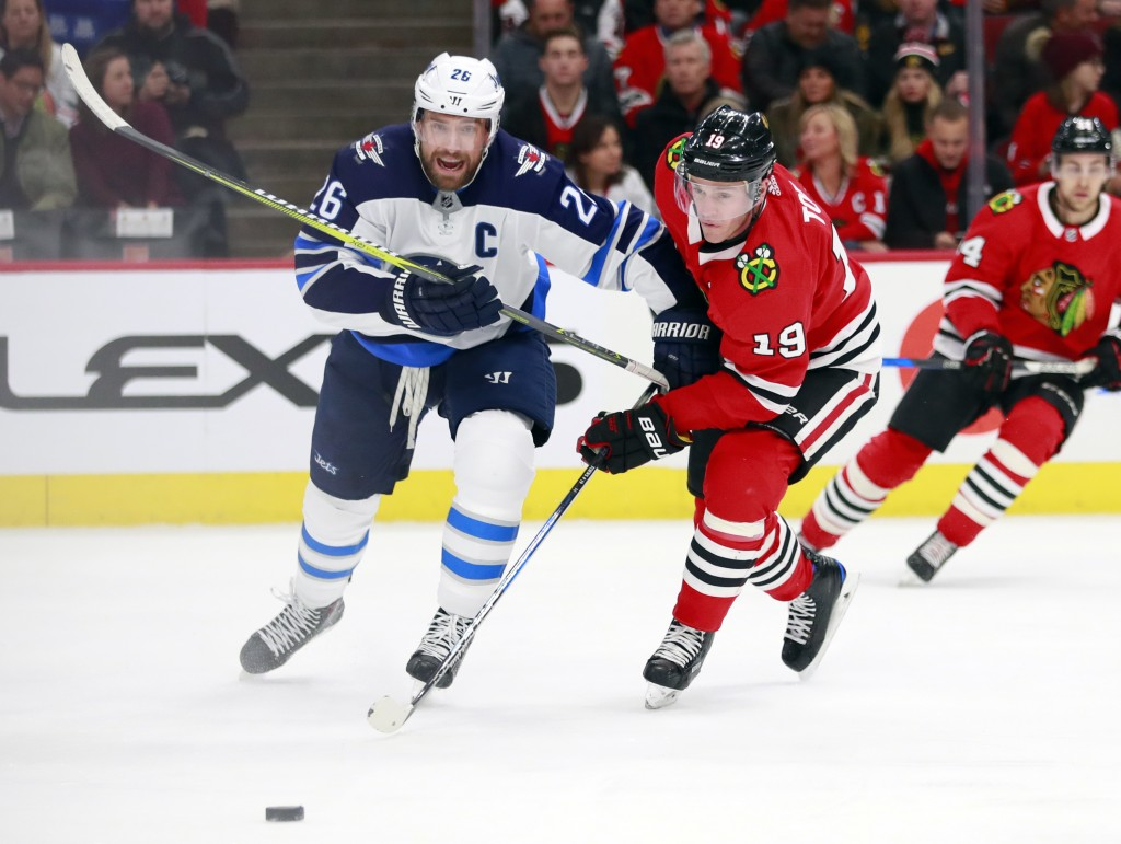 Winnipeg Jets right wing Blake Wheeler (26) and Chicago Blackhawks center Jonathan Toews (19) vie for the puck during the first period of an NHL hocke