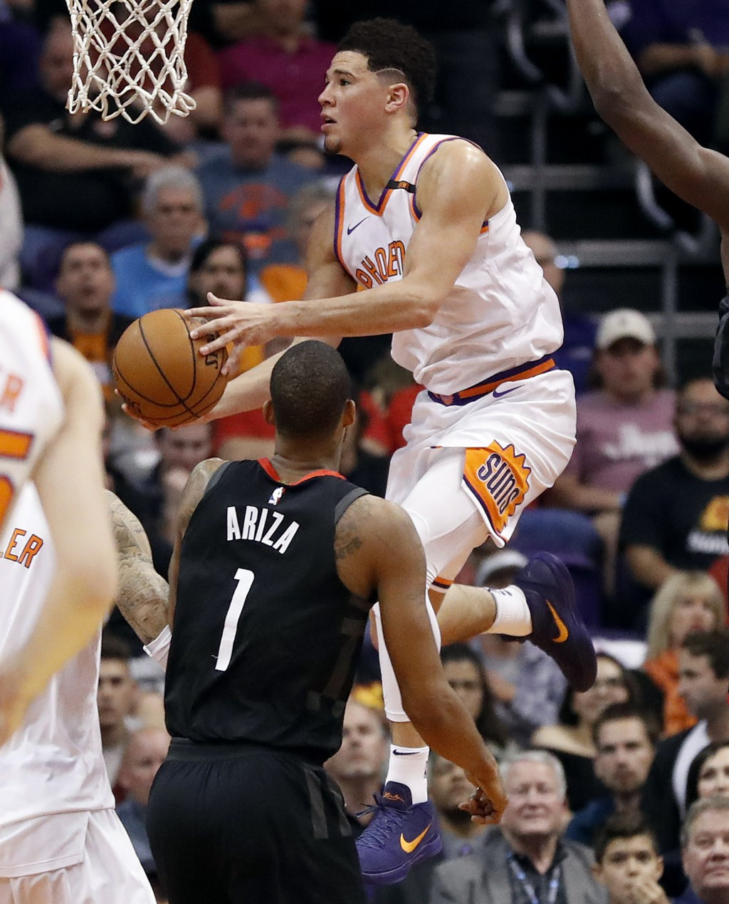 Phoenix Suns guard Devin Booker drives over Houston Rockets forward Trevor Ariza (1) during the first half of an NBA basketball game, Friday, Jan. 12,