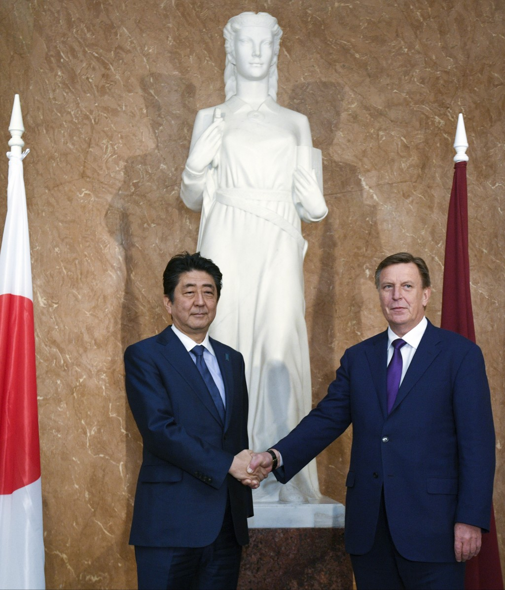 Japanese Prime Minister Shinzo Abe, left, and Latvian Prime Minister Maris Kucinskis shake hands as they pose for a photo prior to their talks in Riga