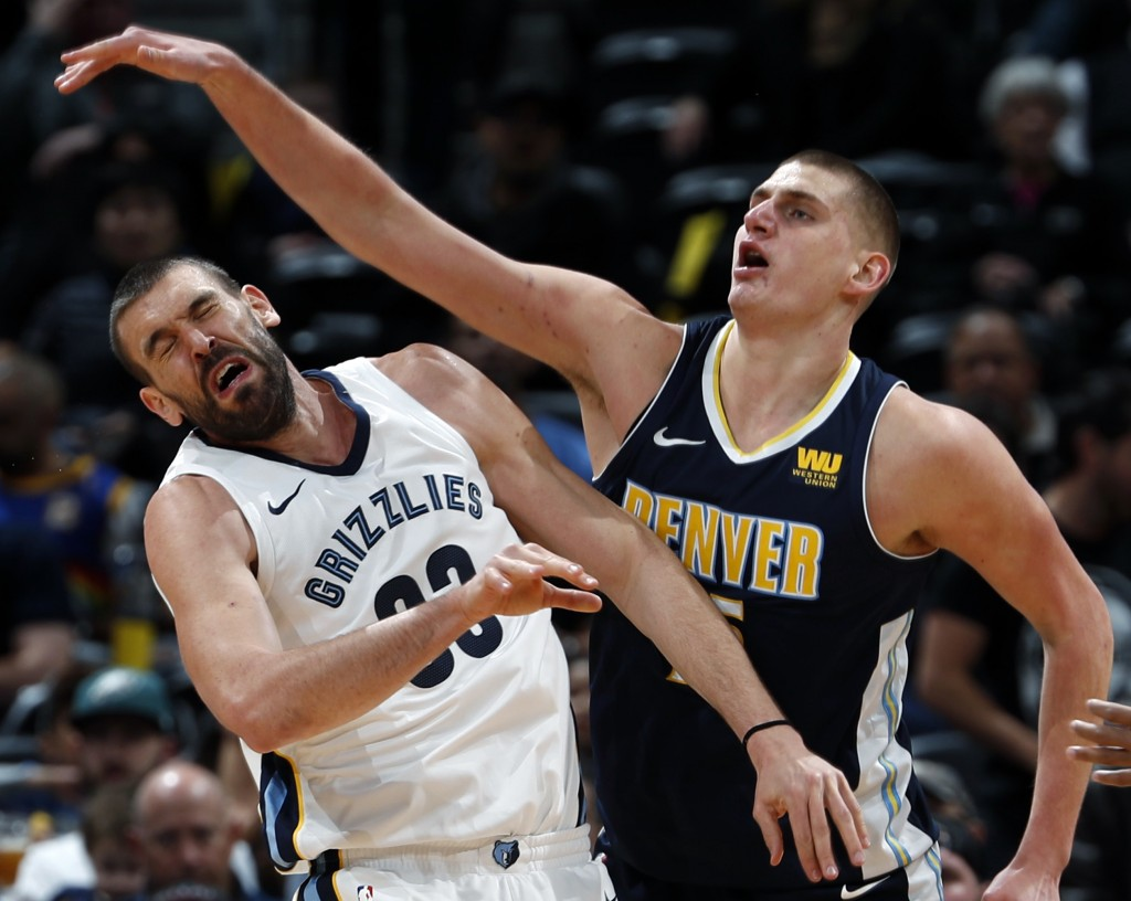 Memphis Grizzlies center Marc Gasol, left, of Spain, reacts after he was hit on the head while fighting for a rebound with Denver Nuggets center Nikol