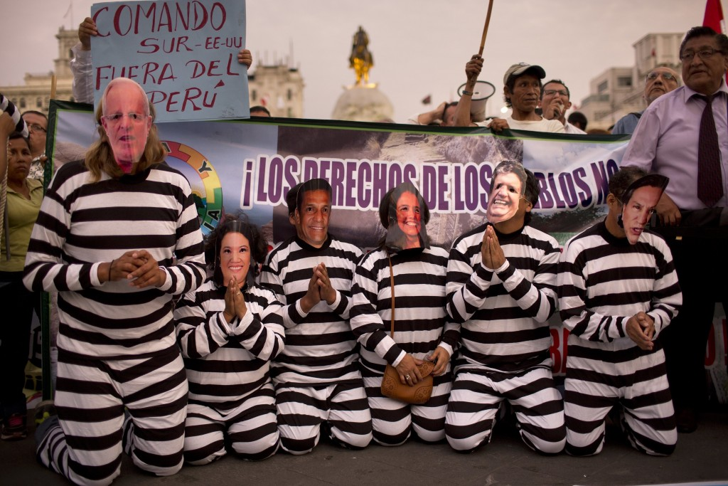 FILE - In this Jan. 19, 2017 file photo, people wearing masks of Peruvian politicians pretend to be prisoners during a protest calling for justice aft