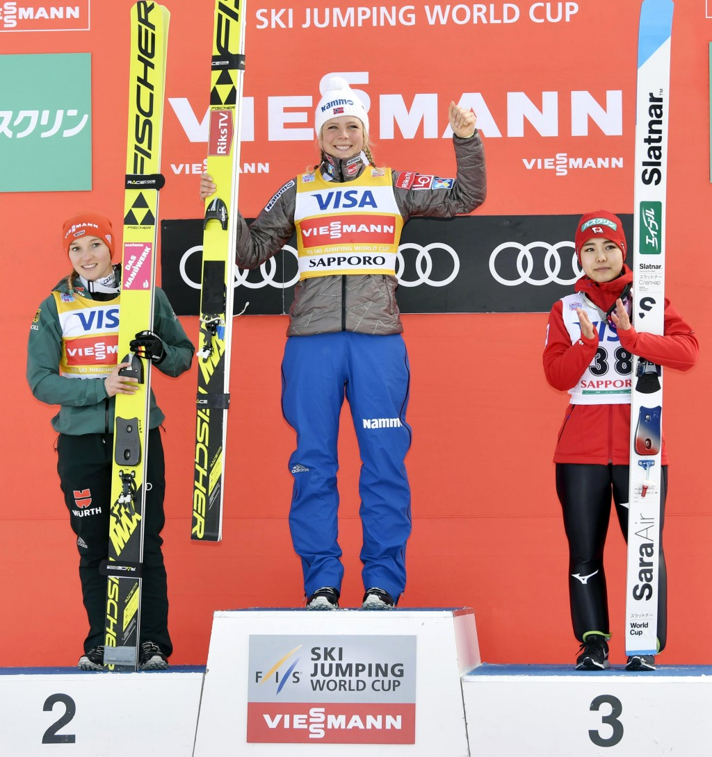 Maren Lundby of Norway, center, celebrates her win on the podium, along with second placed Germany's Katharina Althaus and third placed Japan's Sara T