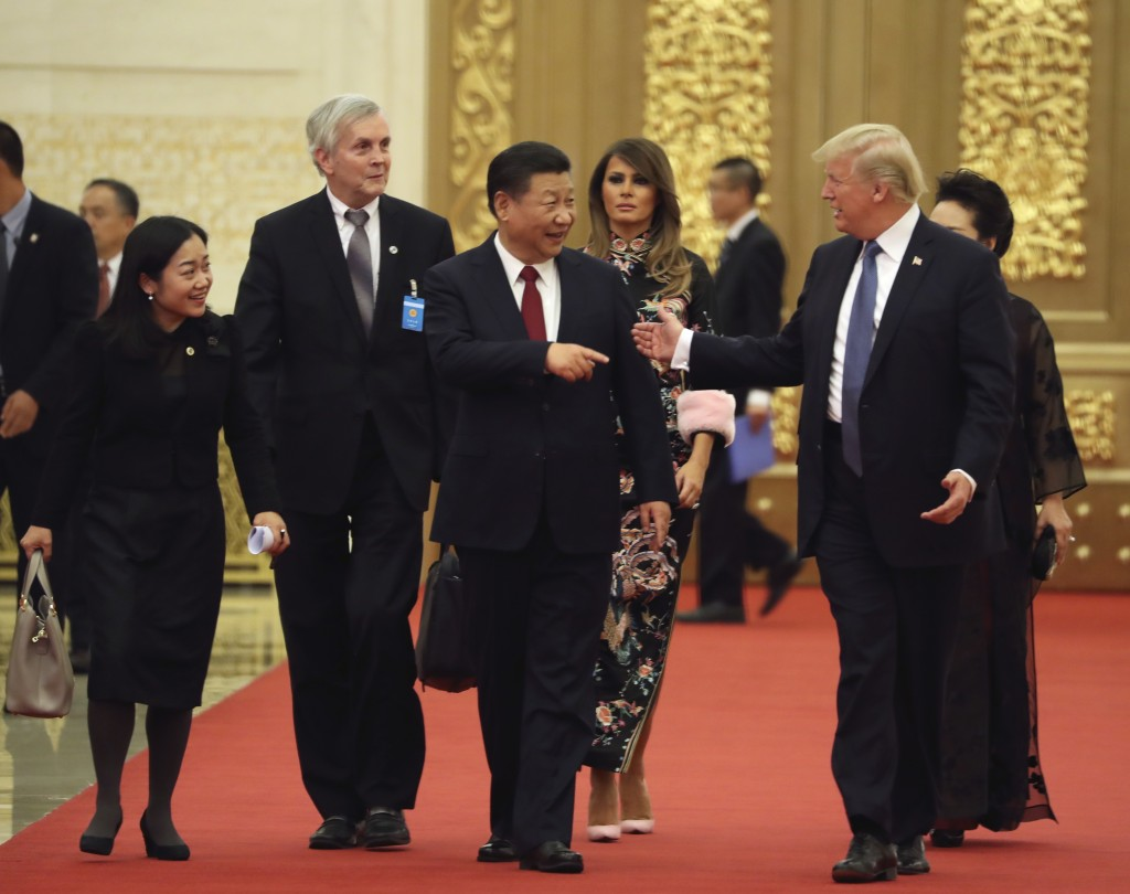 FILE - In this Nov. 9, 2017, file photo, President Donald Trump and Chinese President Xi Jinping, center, talk to each other as they arrive for a stat