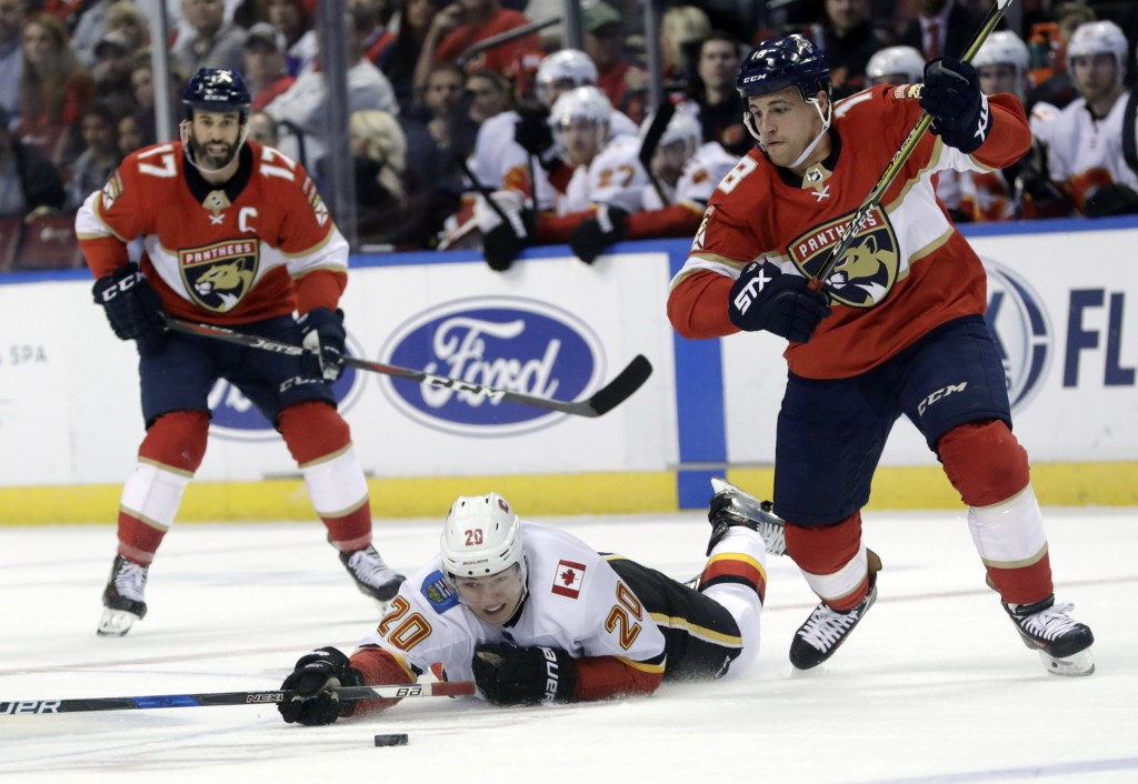 Calgary Flames' Curtis Lazar (20) falls to the ice as he goes for the puck against Florida Panthers' Micheal Haleym, right, during the first period of
