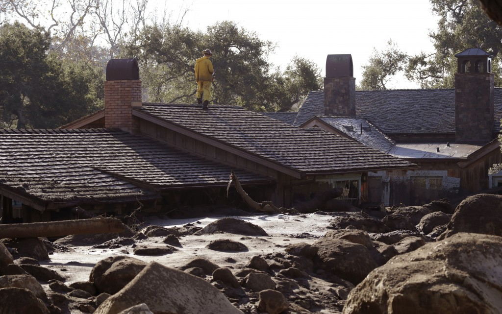 A Cal Fire search and rescue crew looks over a home damaged by storms in Montecito, Calif., Friday, Jan. 12, 2018.  The mudslide, touched off by heavy