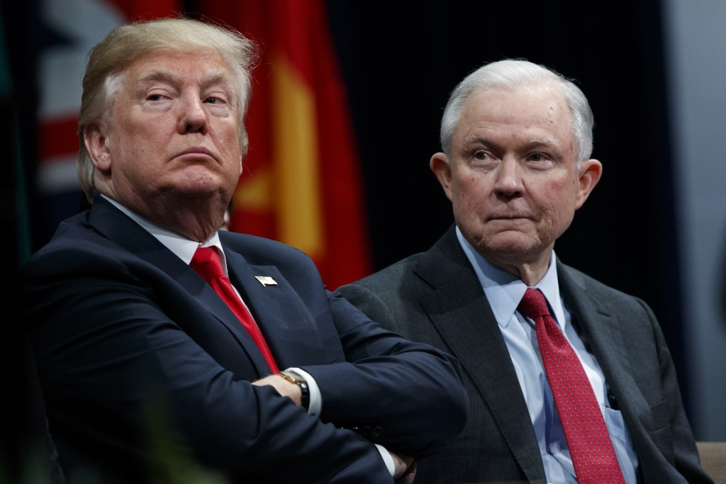 FILE - In this Dec. 15, 2017, file photo, President Donald Trump sits with Attorney General Jeff Sessions during the FBI National Academy graduation c