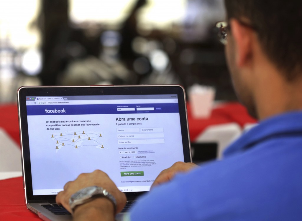 FILE - In this Thursday, Jan. 4, 2018, file photo, a man demonstrates how he enters his Facebook page as he works on his computer at a restaurant in B