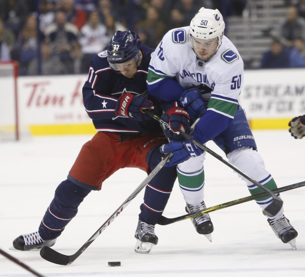Columbus Blue Jackets' Markus Hannikainen, left, of Finland, and Vancouver Canucks' Brendan Gaunce fight for the puck during the first period of an NH