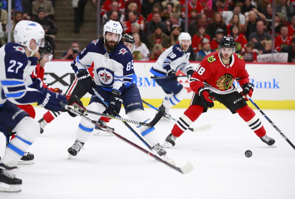 Winnipeg Jets center Mathieu Perreault (85) makes a pass to left wing Nikolaj Ehlers (27) as Chicago Blackhawks left wing Vinnie Hinostroza (48) watch
