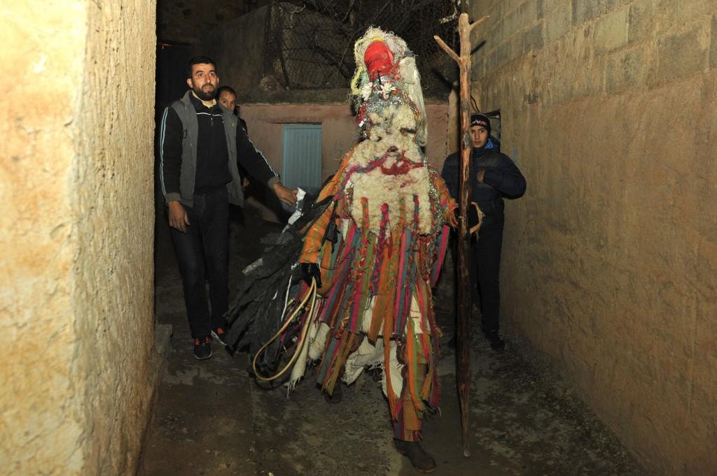 A man dressed in an animal-hide costume of the Ayred festival walks through the village of Beni Snous, south of Tlemcen, Algeria, Thursday, Dec.11, 20
