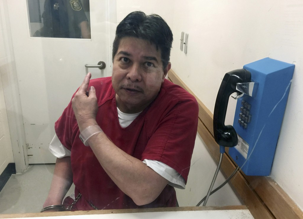 FILE - In this Nov. 17, 2017, file photo, escaped hospital patient Randall Saito points to a guard as he sits in an inmate visitor's booth at San Joaq