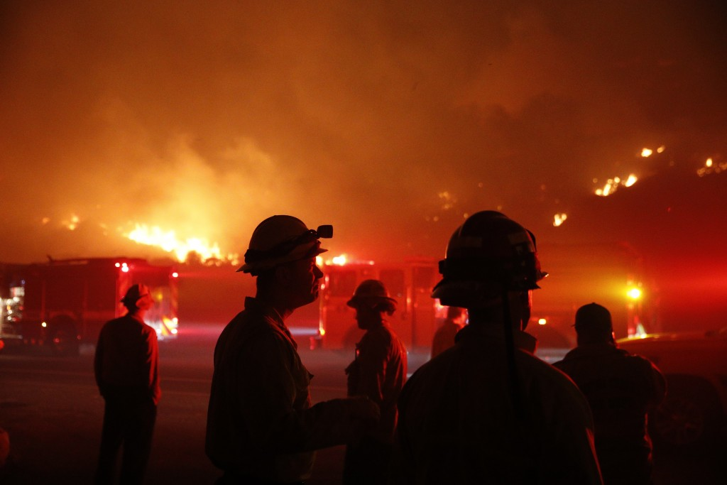 FILE - In this Dec. 5, 2017 file photo, firefighters gather in front of a residential area as a wildfire burns along the 101 Freeway in Ventura, Calif