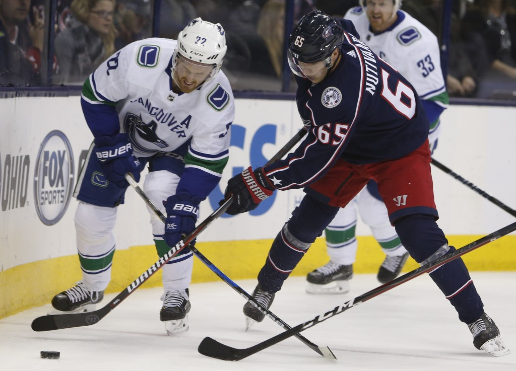 Vancouver Canucks' Daniel Sedin, left, of Sweden, and Columbus Blue Jackets' Markus Nutivaara, of Finland, fight for a the puck during the first perio