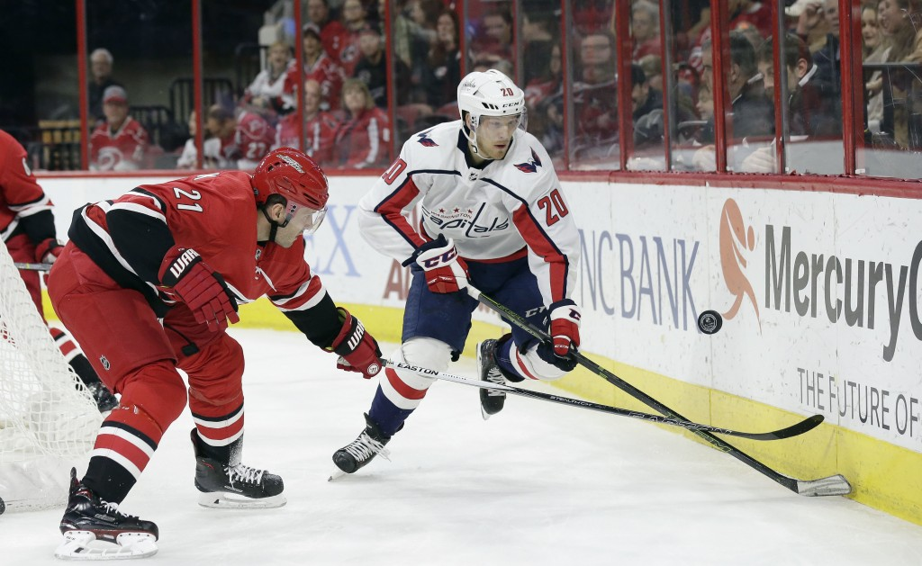 Washington Capitals' Lars Eller (20), of Denmark, and Carolina Hurricanes' Lee Stempniak (21) chase the puck during the first period of an NHL hockey