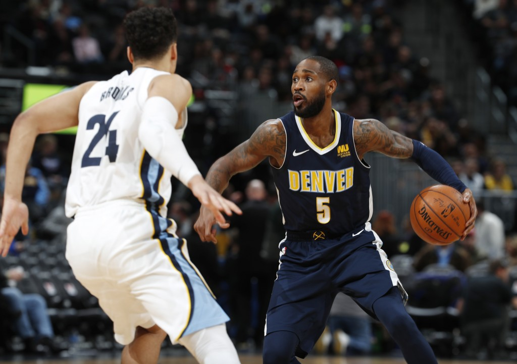 Denver Nuggets guard Will Barton, right, looks to pass the ball as Memphis Grizzlies forward Dillon Brooks defends in the second half of an NBA basket
