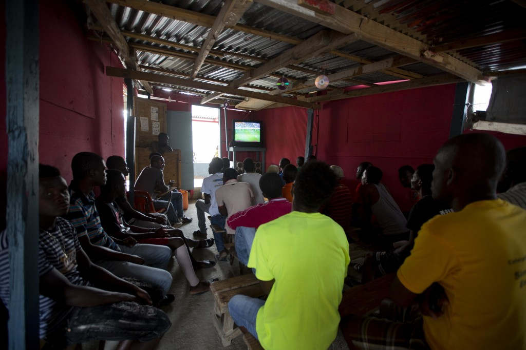 In this Wednesday, Jan. 10, 2018 photo, residents watch soccer in a shelter that has evolved into a business where residents can charge their cellphon