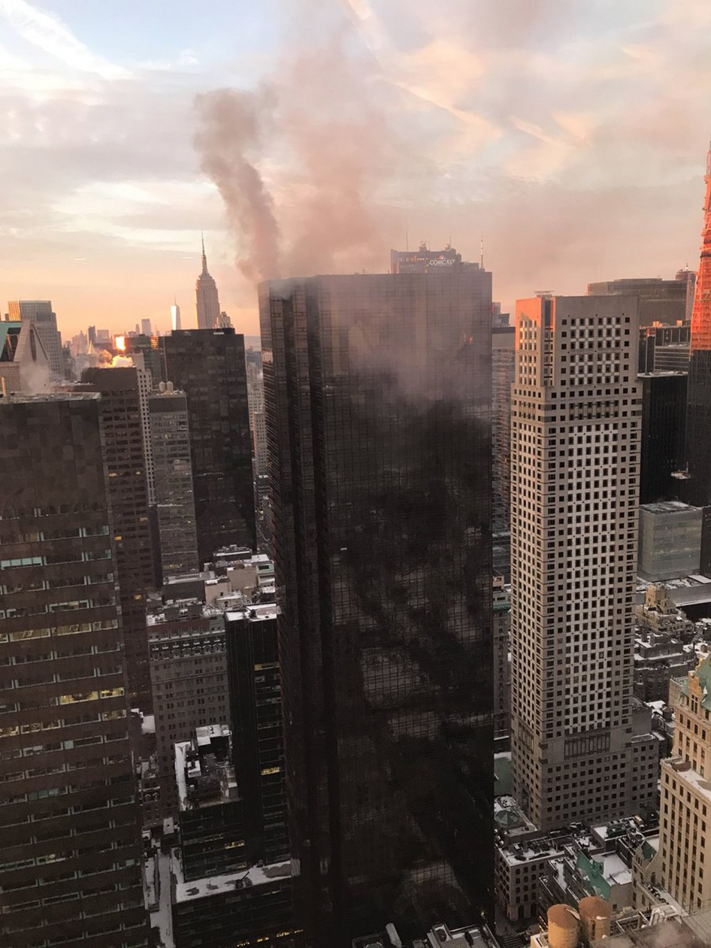 FILE - In this Monday, Jan. 8, 2018 file photo, smoke rises from Trump Tower in New York. The Associated Press has found that stories circulating on t