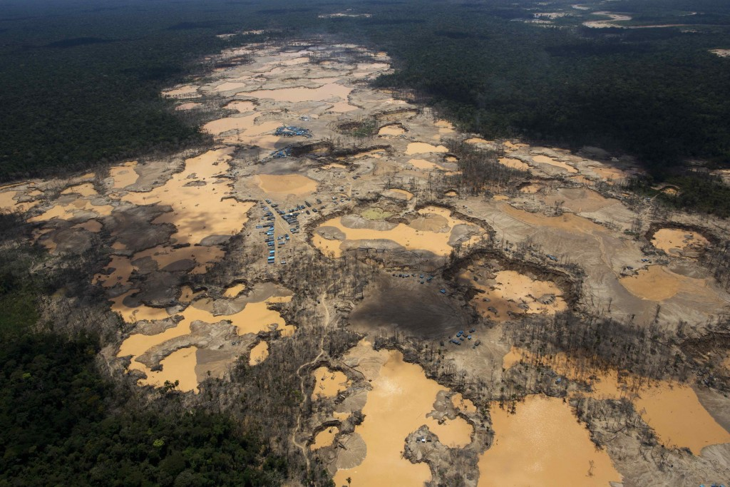 FILE - This Nov. 11, 2014 file photo shows a deforested area dotted with blue tarps, marking the area where miners reside, and craters filled with wat