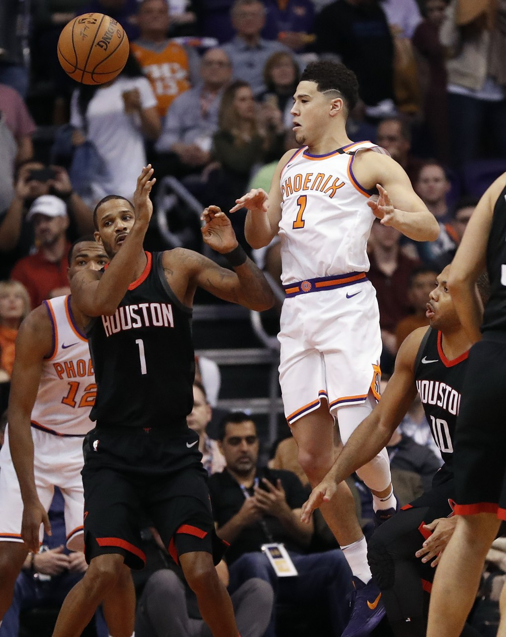 Phoenix Suns guard Devin Booker passes the ball past Houston Rockets forward Trevor Ariza,front  left, during the first half of an NBA basketball game