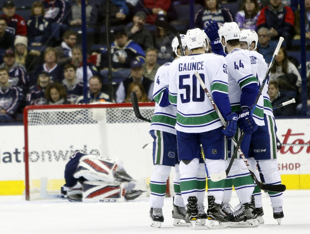 Vancouver Canucks players celebrate their goal against Columbus Blue Jackets' Sergei Bobrovsky, of Russia, during the second period of an NHL hockey g
