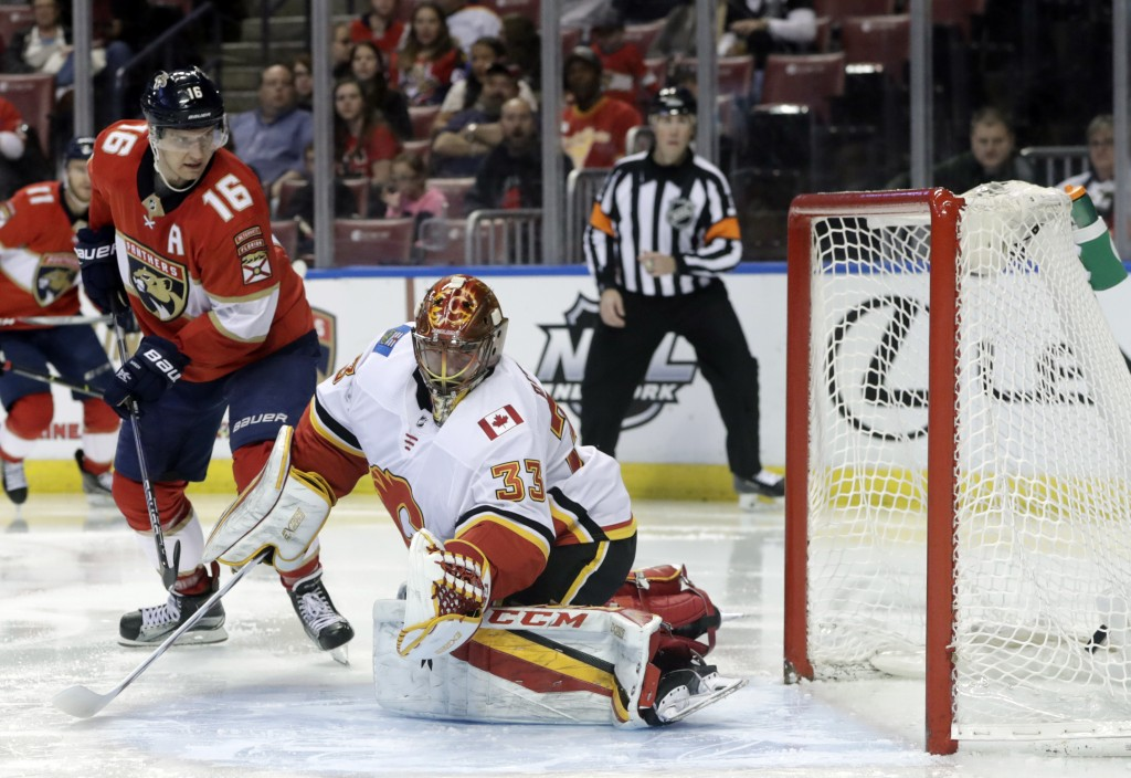 The puck gets past Calgary Flames goaltender David Rittich (33) on a goal by Florida Panthers' Evgenii Dadonov, not seen, as Aleksander Barkov (16) wa