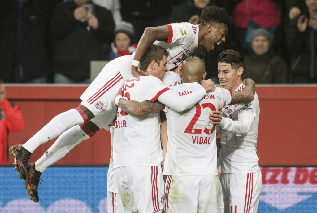 Bayern's David Alaba, top, celebrates the first goal of the game acored by Javi Martinez, obscured, during the German Bundesliga soccer match between