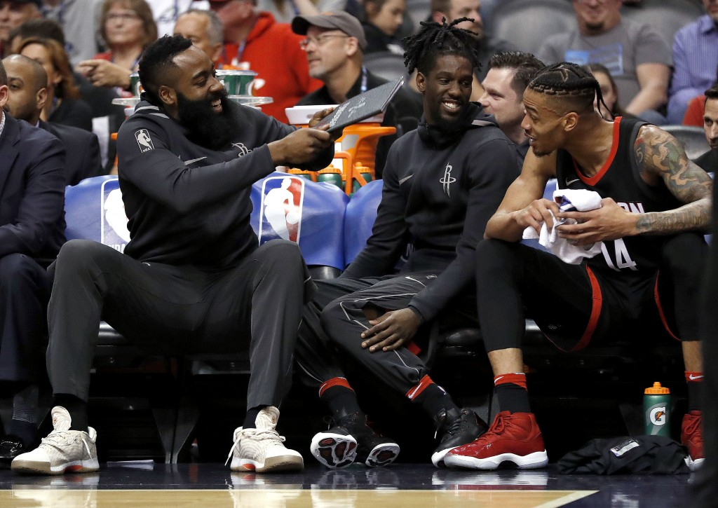 Houston Rockets guard James Harden, left, playfully fans his teammates on the bench during the first half of the team's NBA basketball game against th