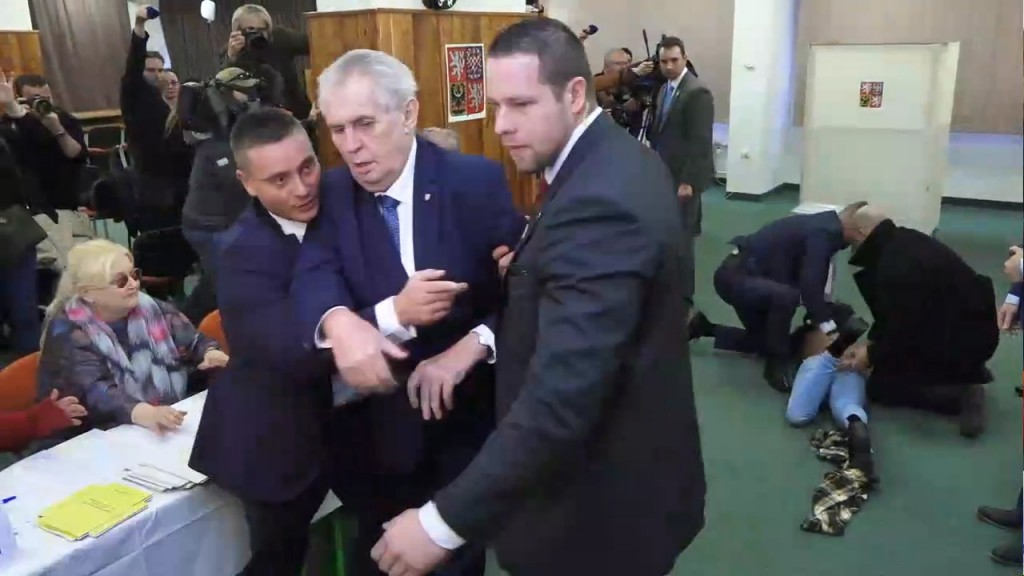 This video frame shows Czech President Milos Zeman, in front, being taken away by security officers as their colleagues, right in the background, inte