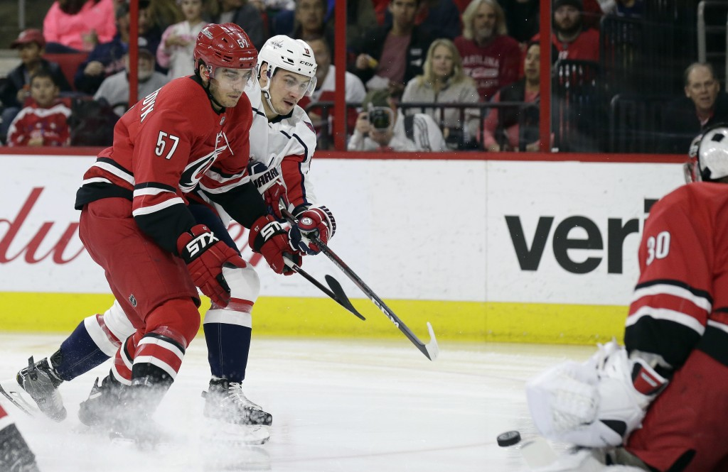 Washington Capitals' Dmitry Orlov, of Russia, shoots against Carolina Hurricanes goalie Cam Ward as Hurricanes' Trevor van Riemsdyk (57) defends durin