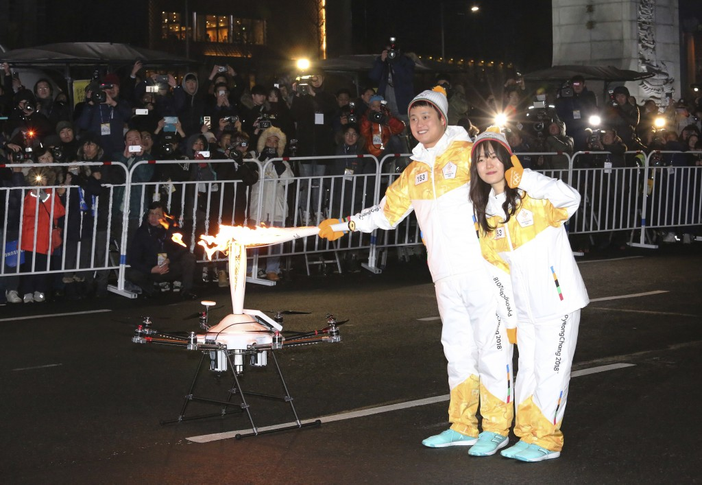 Torch bearers pose as they pass the Olympic flame to a drone during the Olympic Torch Relay in Seoul, South Korea, Saturday, Jan. 13, 2018. South Kore