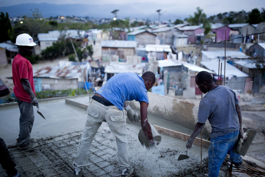 In this Saturday, Jan. 6, 2018 photo, construction workers build a concrete roof in the Caradeux refugee camp set up nearly eight years ago for people