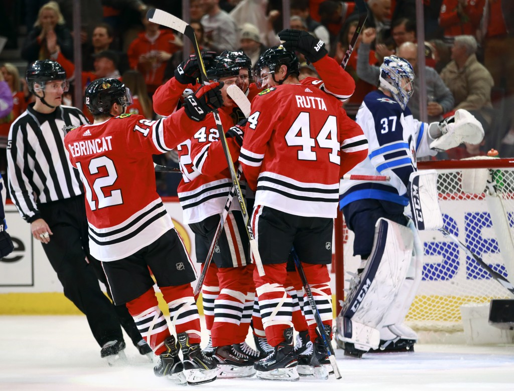 Chicago Blackhawks defenseman Jan Rutta (44) celebrates with teammates after his goal as Winnipeg Jets goaltender Connor Hellebuyck (37) stands in the